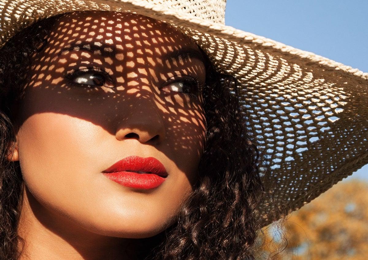 Frau mit Strohhut schatten im Gesicht